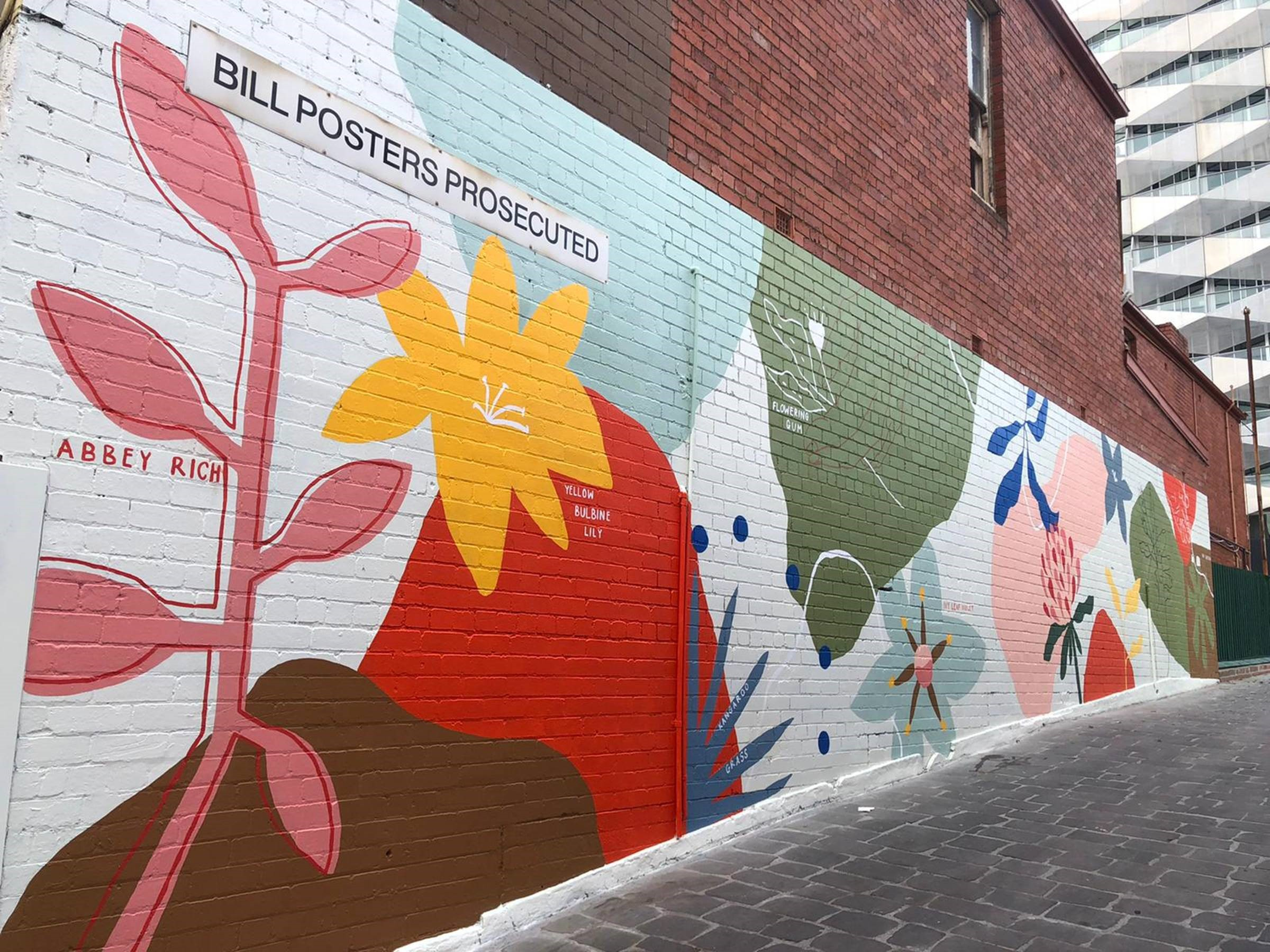 Picture of a brightly coloured floral mural on a brick wall