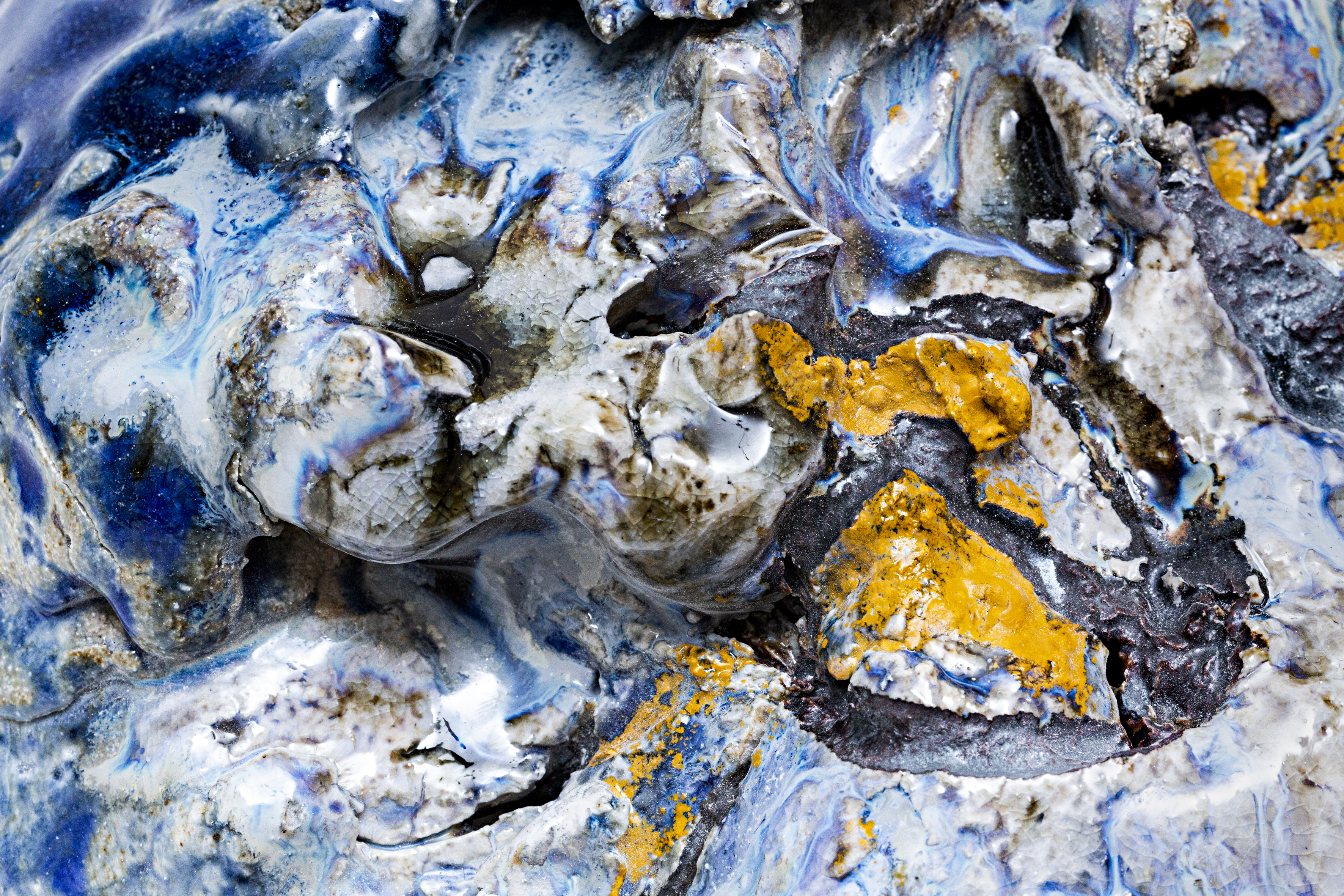 Detailed photograph of blue and yellow glazes on a textured ceramic surface