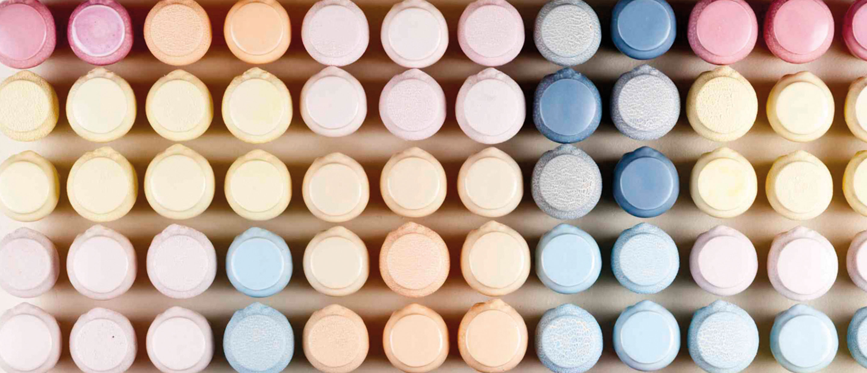 Colourful Ceramic pots organised in gradient by Tina Lee