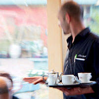Cafe Waiter serving coffee to customers