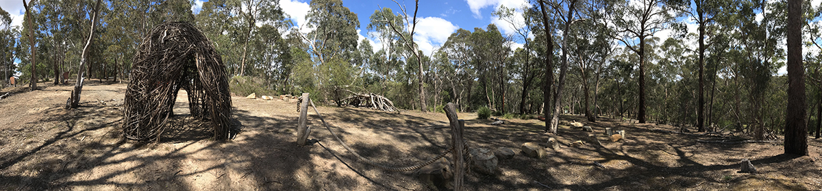 Panorama showing trees and children's play area with tent made of twigs