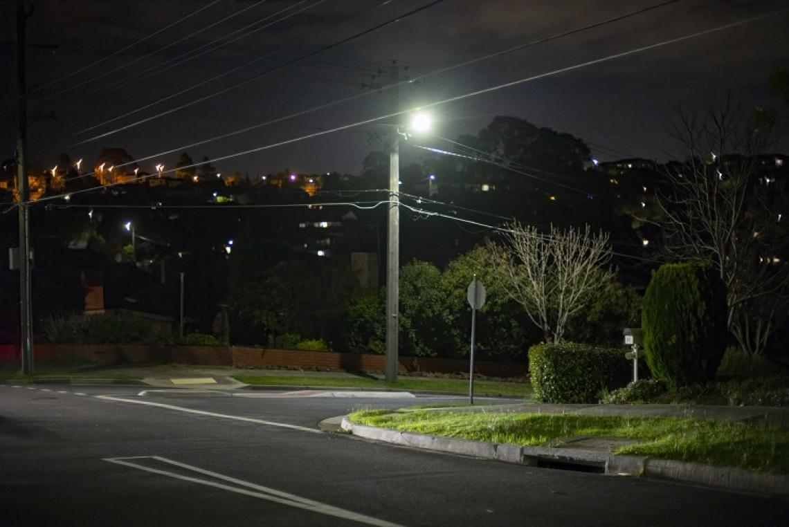 Photograph of a suburban street corner at night with a street light in the centre of frame and electricity wires crossing the image