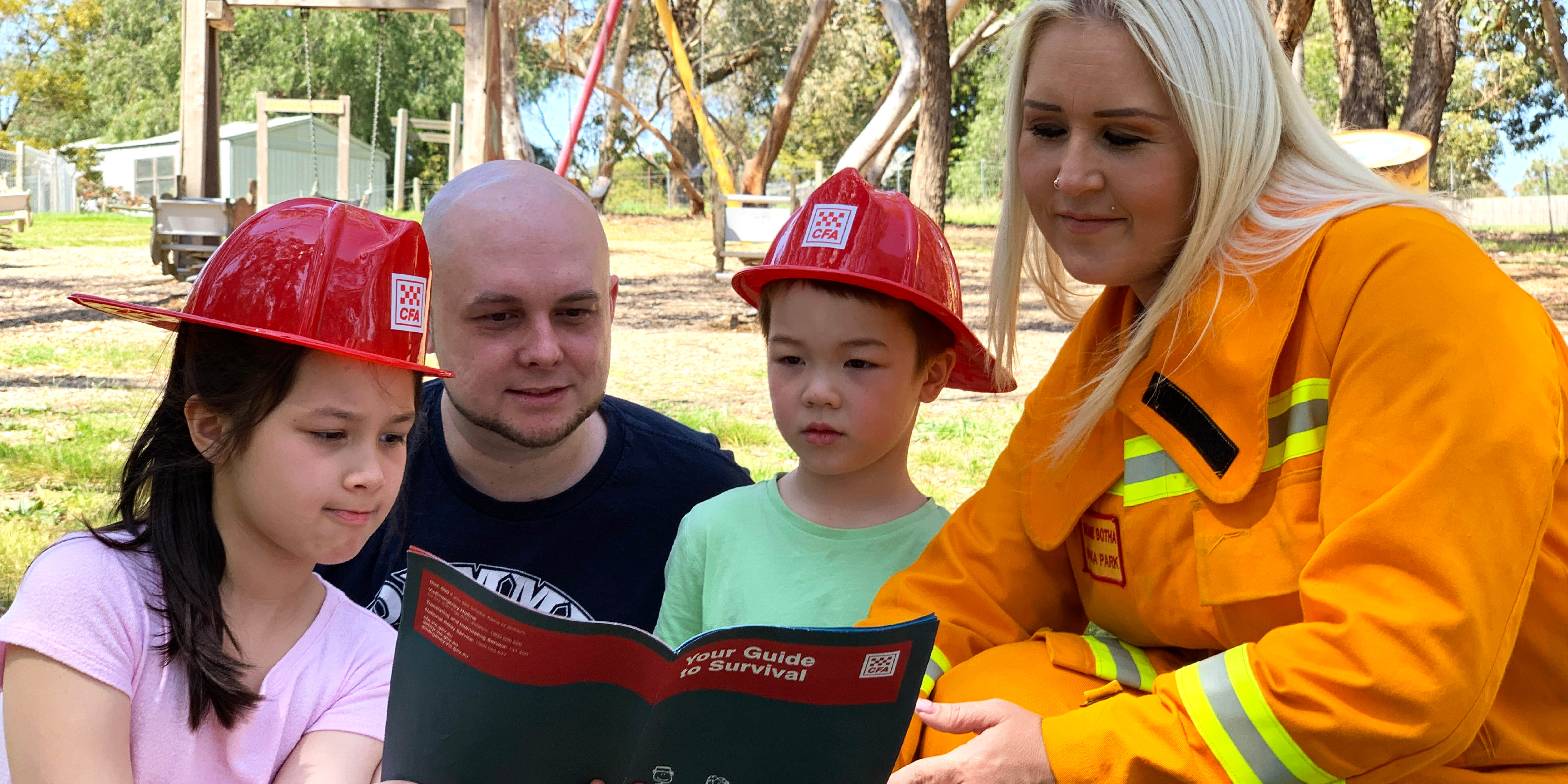 Two emergency workers reading to two kids
