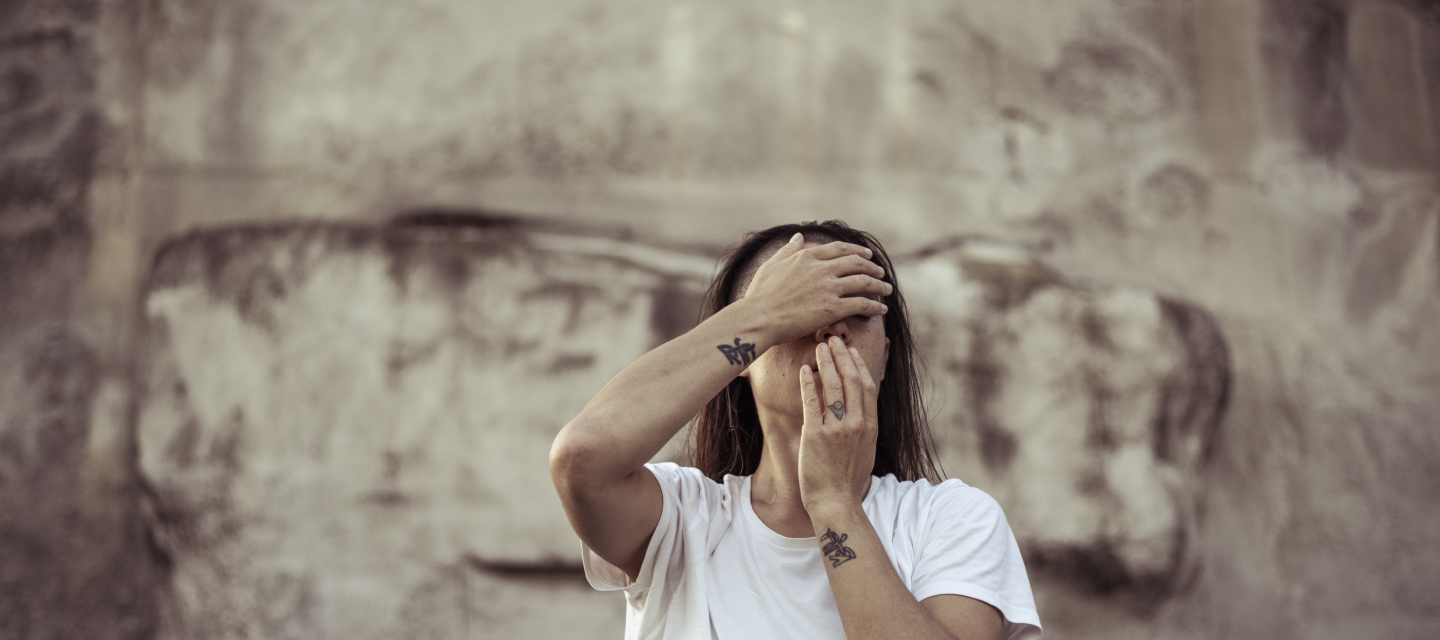 Woman in a white t shirt with tattoos on her wrist holding her hands to her face.
