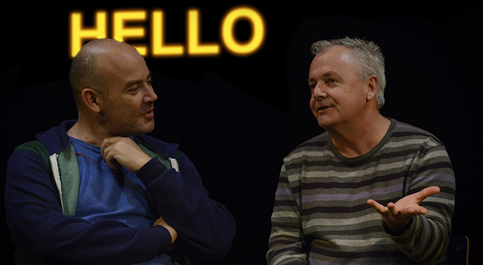 Two men sitting down and speaking with a yellow neon hello sign behind them