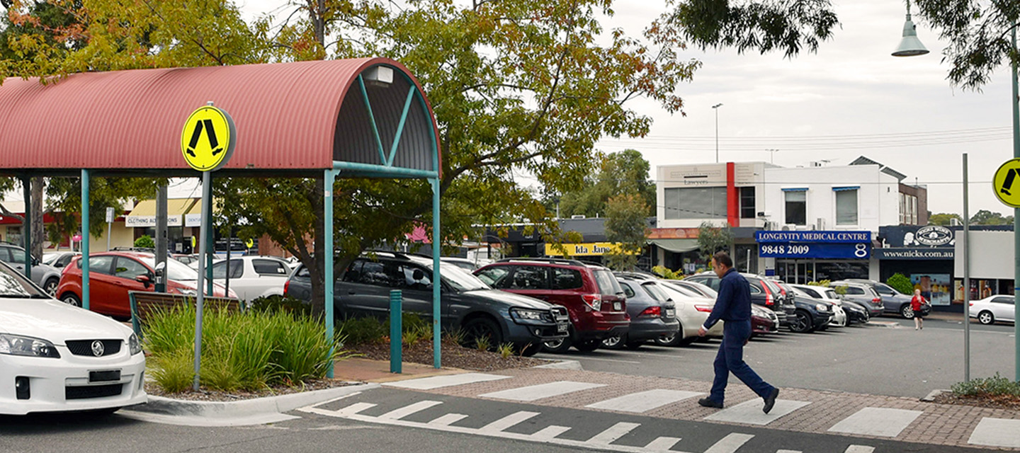 Man walking across pedestrian crossing in carpark of Jackson Court shopping centre