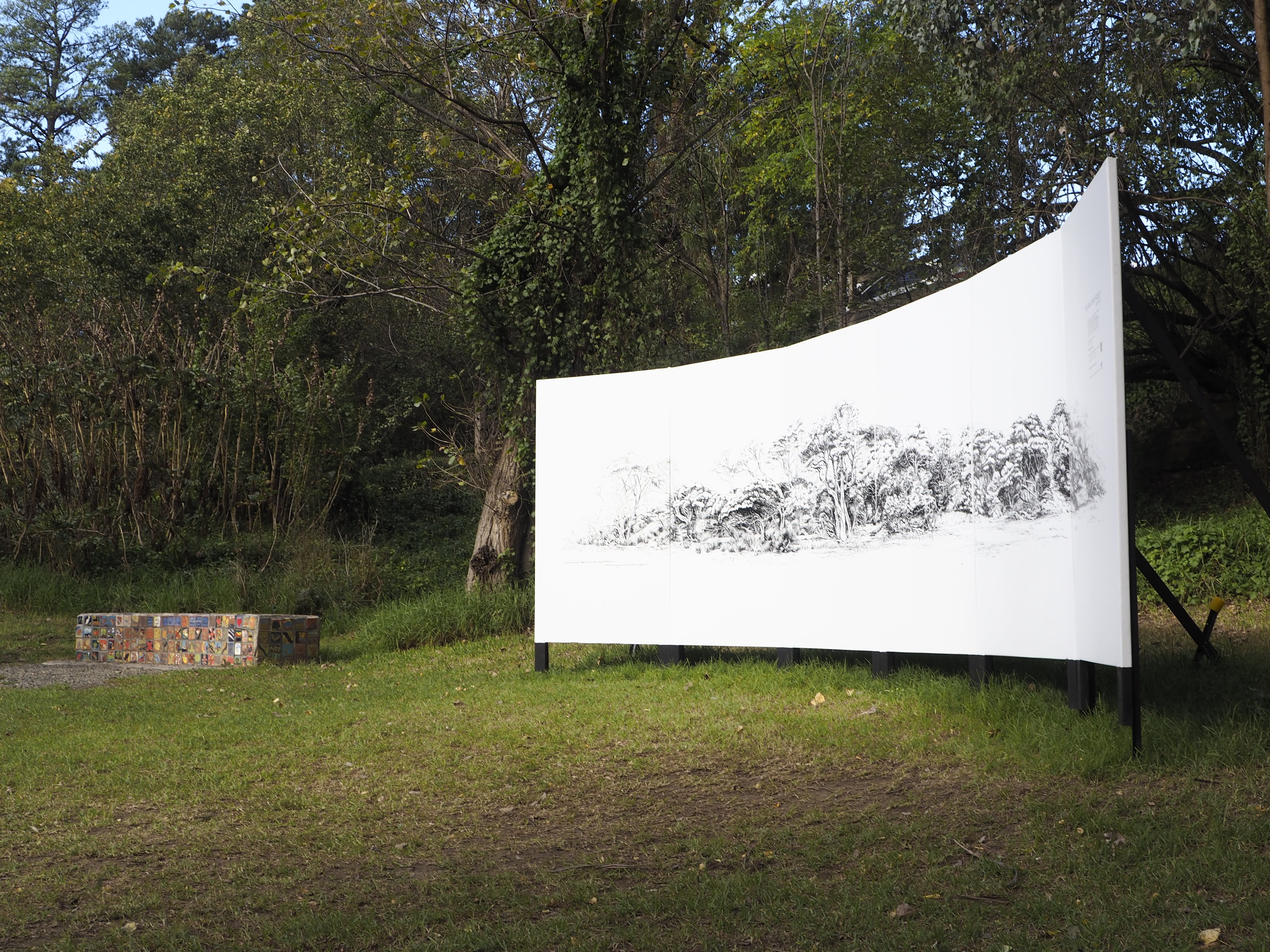Photograph of a curved white billboard featuring a detailed black landscape drawing installed in parkland