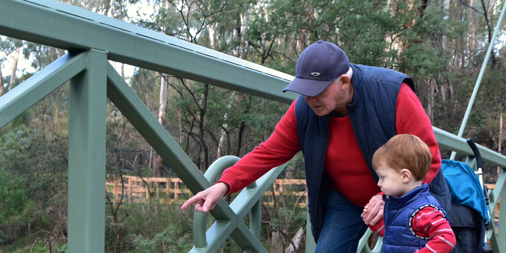 Grandparent and grandchild standing on a bridge looking down at the water below