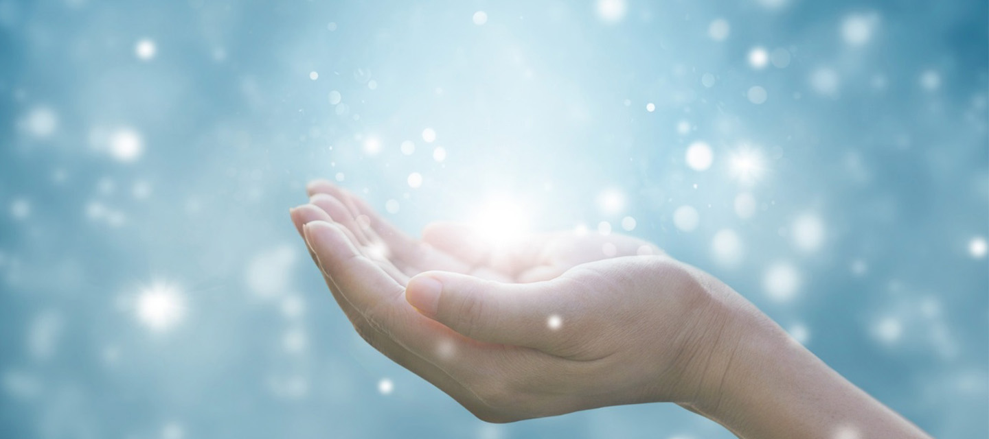 cupped hands within rendering of sparkling light