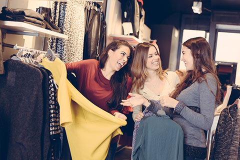 Photo of three females viewing clothes in a local clothes store